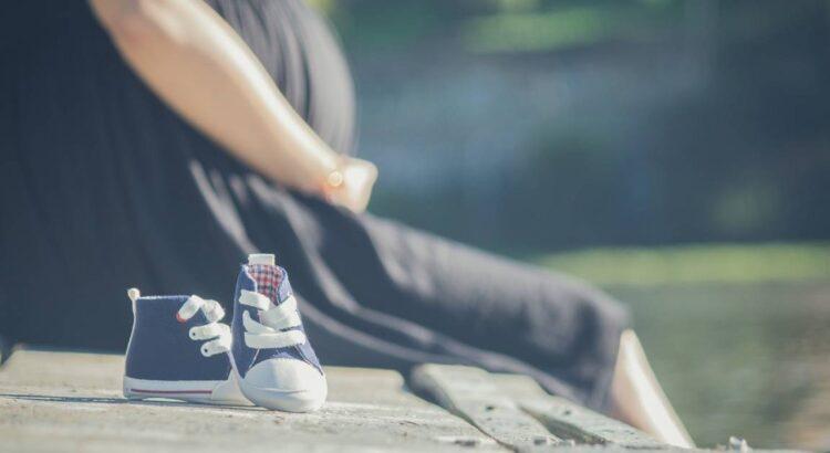 donna incinta con scarpette su di un muretto